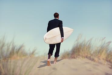 businessmen with surfboards, signs of bleisure impacting travel management companies